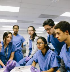 Stanford Medical Youth Science Program participants wear scrubs and gloves in order to help in a laboratory.