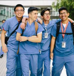 Four Stanford Medical Youth Science Program participants wear scrubs on the medical school campus.
