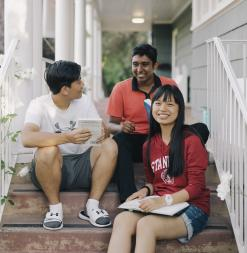 Three participants sit on different steps on the stoop of the SUMaC dorm.