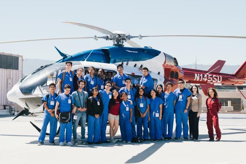 On a helipad used for emergency transportation, a group of participants pose together.