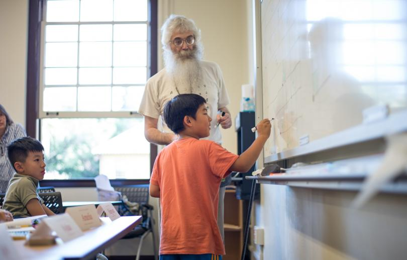 An instructor works with a young student at the whiteboard during a Stanford Math Circle session.